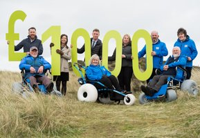 Beach wheelchairs and volunteers holding £1000 sign in the sand dunes