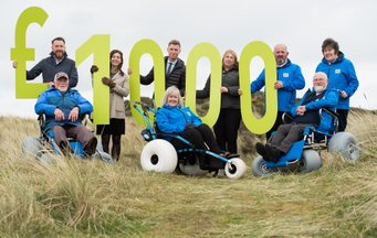 Beach wheelchair volunteers holding £1000 sign in the sand dunes